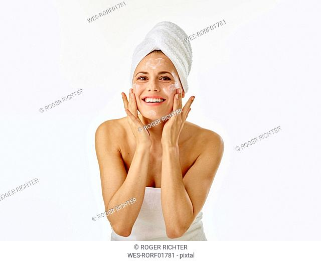 Young woman applying face cream on her face