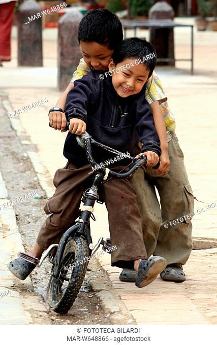 NEPAL Bodhnat, davanti alla stupa principale due fratelli giocano in bicicletta maggio 2009,,Copyright © Fototeca Gilardi
