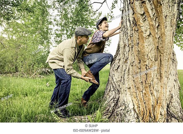 Side view of man helping smiling boy climb tree