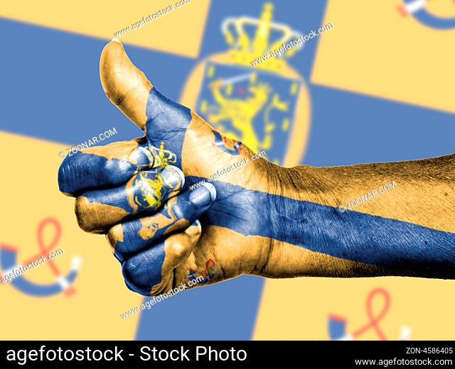 Old woman with arthritis giving the thumbs up sign, wrapped in flag pattern, kingdom of the Netherlands