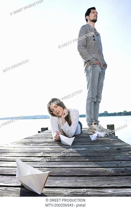 Young couple lake wooden jetty relaxing model boat