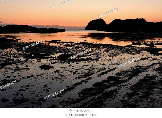 Sunset over bay of Kintra, Isle of Mull, Scotland, reflected in tidal pools