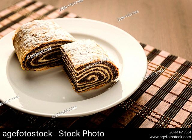 strudel with poppy seeds on a ceramic white plate on wooden background