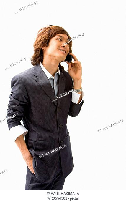 Young Asian business man with mobile phone calling, isolated