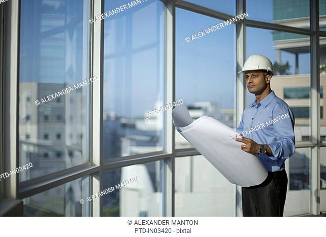Singapore, Male architect with hardhat and building plans looking through window