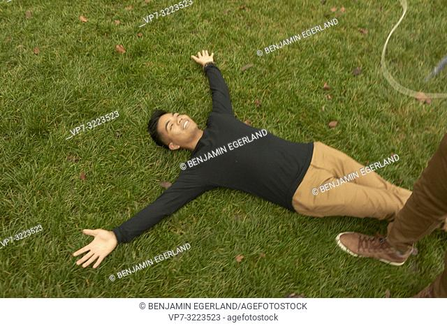 man laying on meadow, relaxing, in Munich, Germany