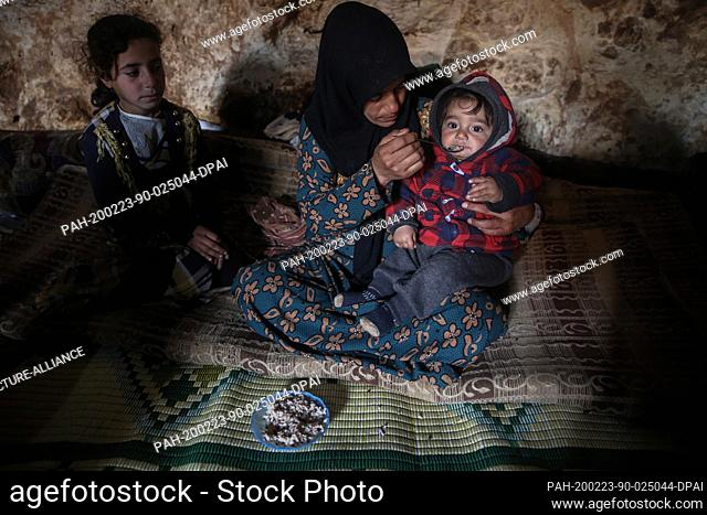 23 February 2020, Syria, Idlib: A Syrian woman feeds a child as she sits inside a cave at Taltouna village. At least eight families live in an ancient deserted...