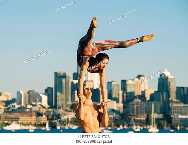Teenage girl and young man, outdoors, woman balancing on man's hands in yoga position