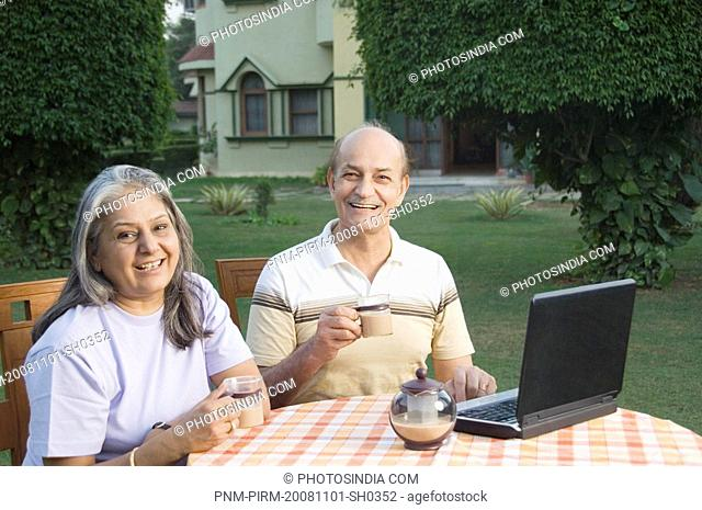 Couple using a laptop and drinking tea in a garden, New Delhi, India