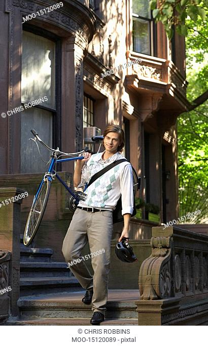Man carrying bicycle descending steps