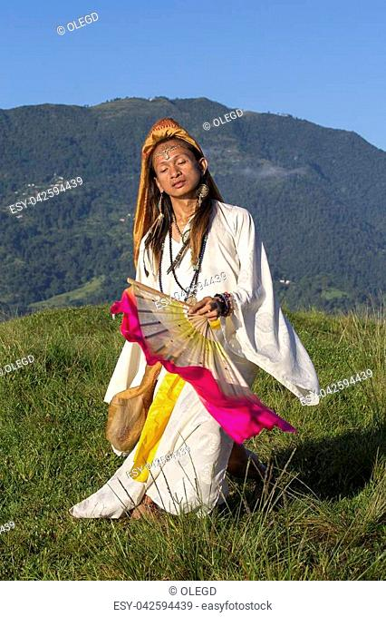 Sirena Sabiha dancing with a fan at sunrise in Pokhara, Nepal. Sirena was born in the Philippines. Close up