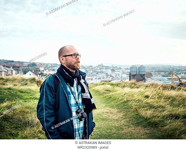 Thoughtful man with camera standing on grassy hill against sky