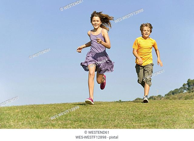 Boy 8-9 and girl 10-11 running together