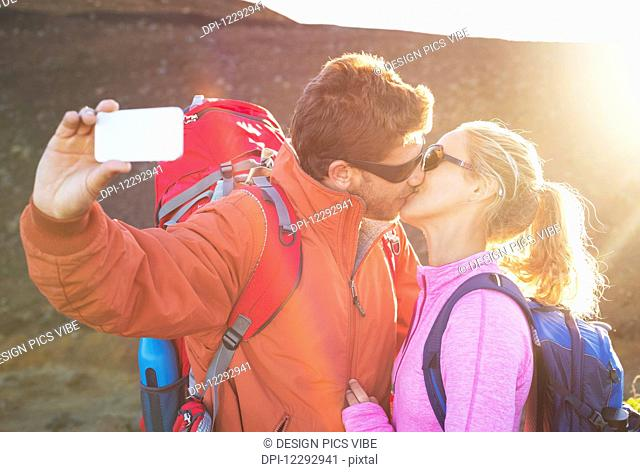 Happy couple taking photo of themselves with smart phone outdoors, Taking a selfie