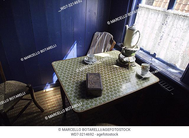 Table with tea cups, in a small room with a blue wall of a fishing village house in Enkhuizen, norther Holland