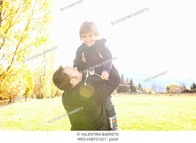 Father holding happy son outdoors