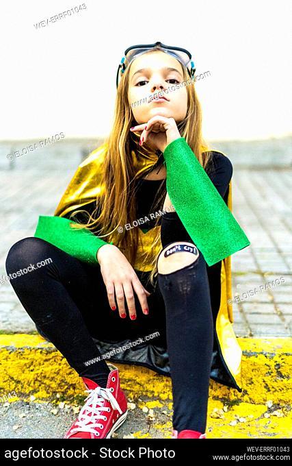 Girl posing in super heroine costume sitting on curb