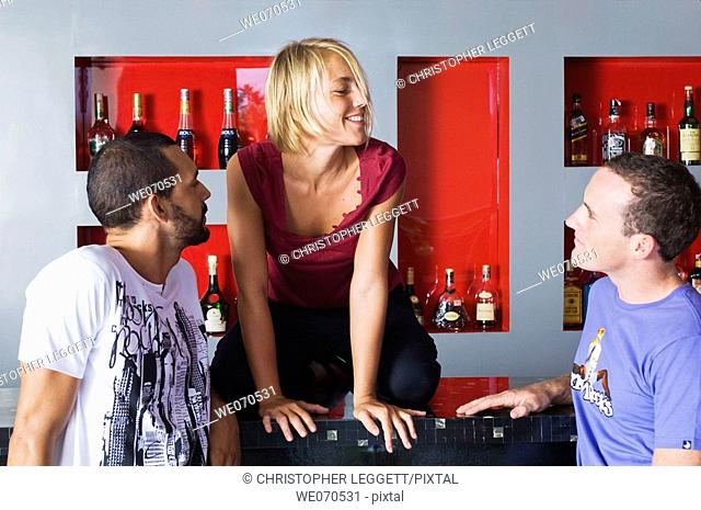 Two men looking at woman on bar counter