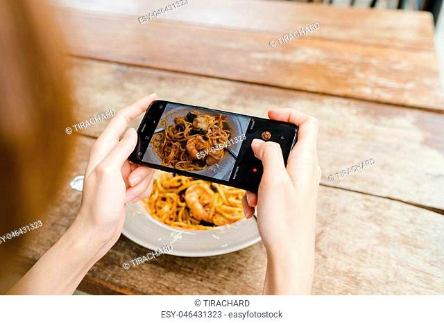 Female blogger photographing lunch in restaurant with her phone. A young woman taking photo of spaghetti food on smartphone