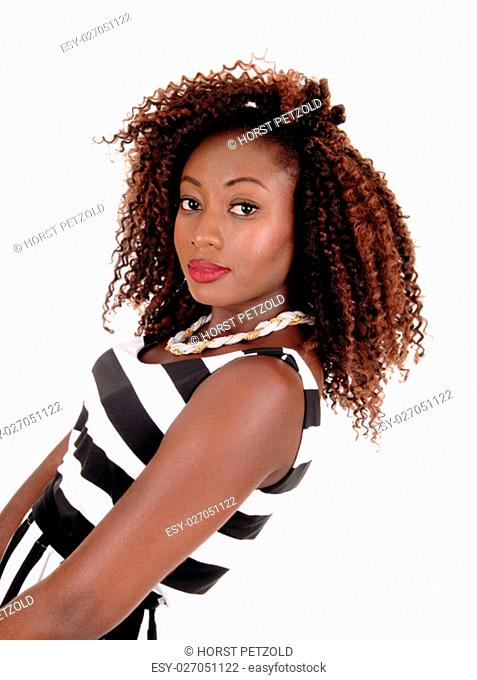 A gorgeous young African American woman standing in a black and white.jumpsuit and bending back, isolated for white background.
