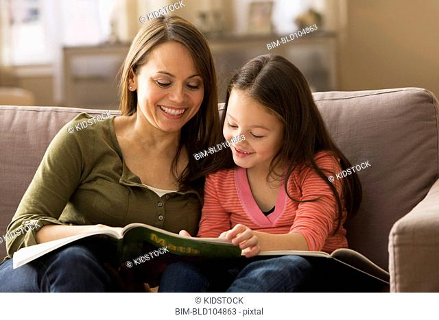 Caucasian mother and daughter reading book together
