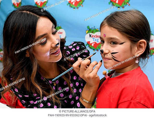 "19 September 2019, Berlin: Verona Pooth puts make-up on a little girl at the """"kinder Tag 2019"""" in Radialsystem V. On the occasion of World Children's Day on..."