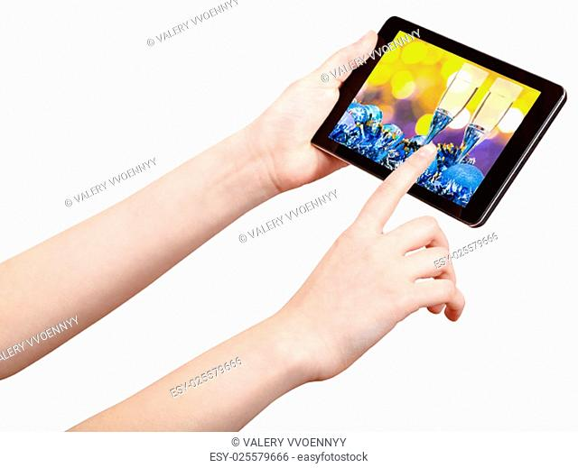 hand touches tablet pc with Christmas still life on screen isolated on white background
