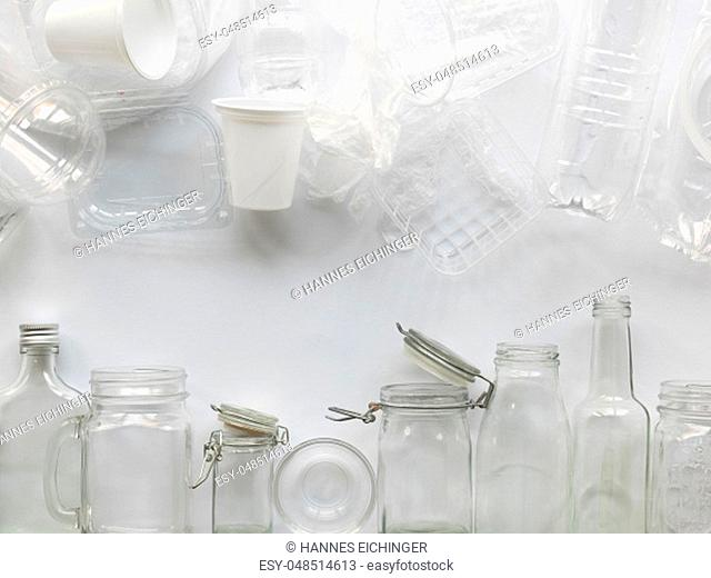 a lot of different empty glass and plastic bottles lying on a white background