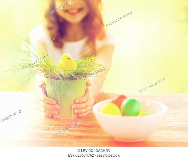 easter, holiday and child concept - close up of girl holding pot with green grass and yellow chicken toy with bowl of colored eggs over green background