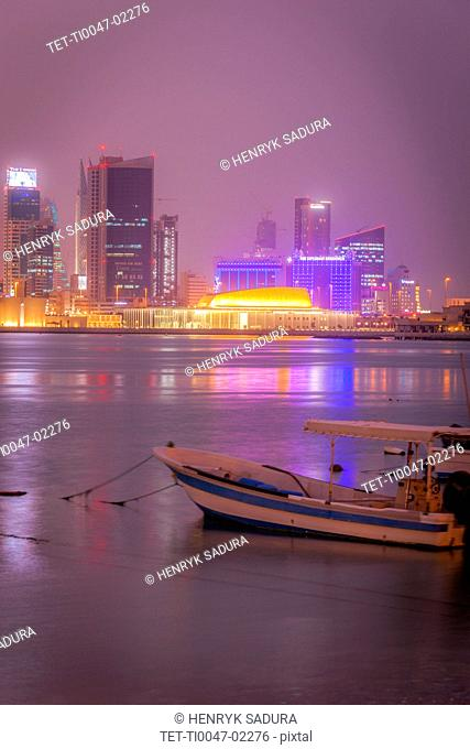 Moored motorboat by city skyline at night in Manama, Bahrain