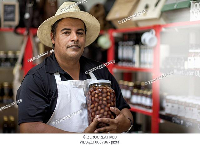 Shopkeeper in shop holding a jar with olives