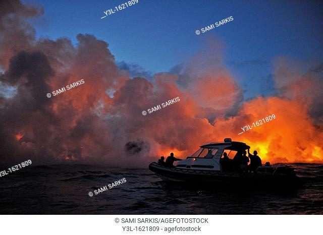 Boat with tourists watching steam rising off lava flowing into ocean at dusk, Kilauea Volcano, Big Island, Hawaii Islands, USA