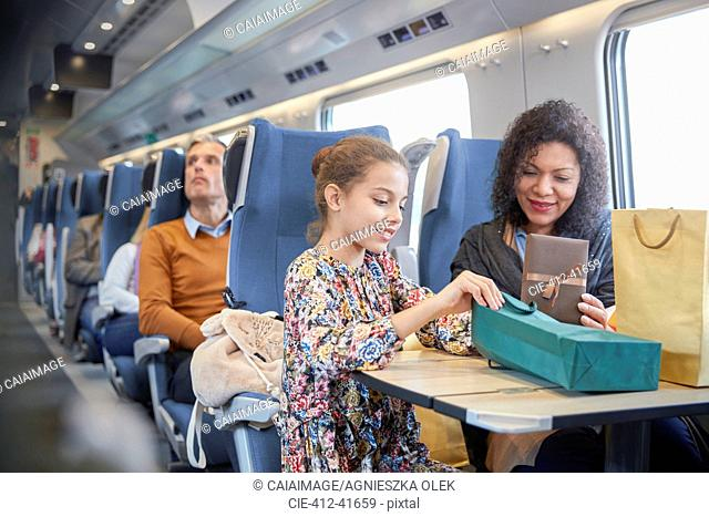 Mother and daughter with shopping bags on passenger train