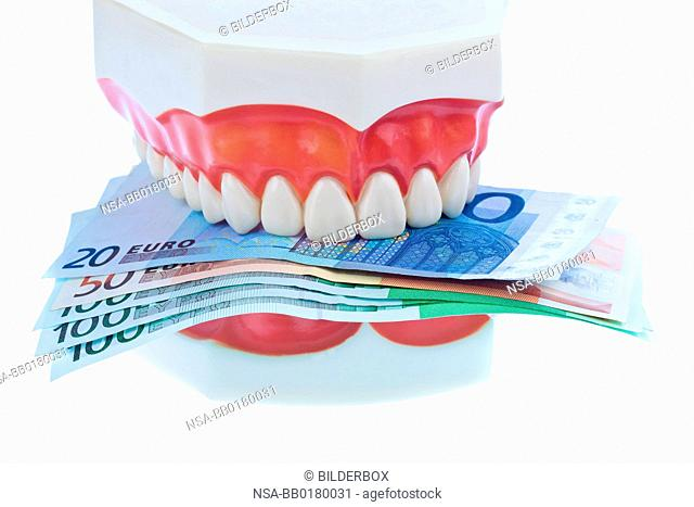 A dental model at the dentist with euro notes.Cost of Health