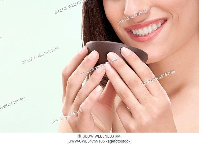 Woman smelling moisturizer cream