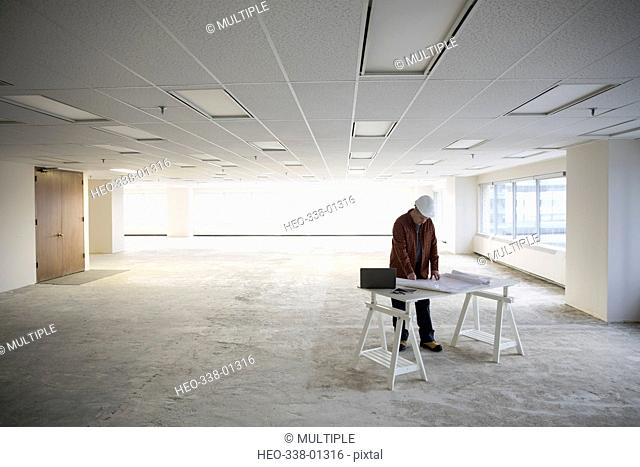 Contractor reviewing blueprints in unfinished, empty open plan office