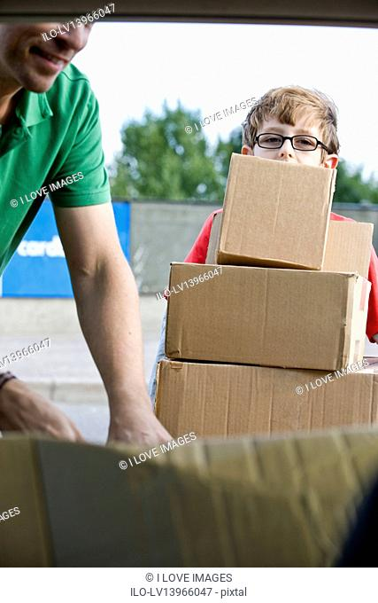 A son helping his father recycle cardboard boxes