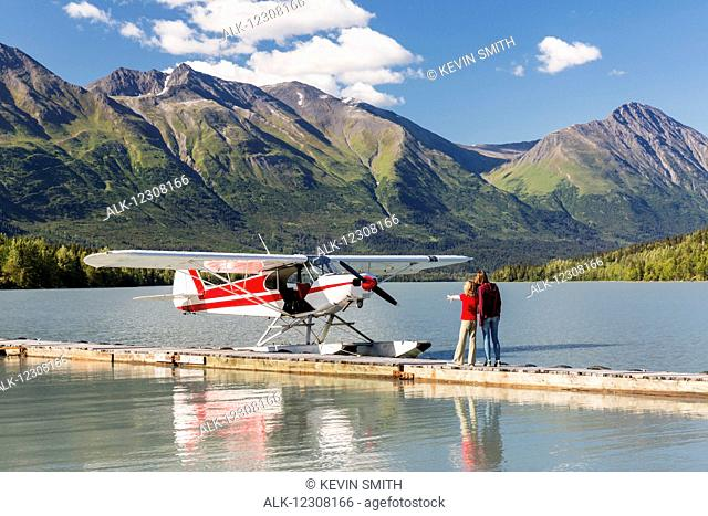 A Mother with her daughter looking at a float plane docked at the Trail Lake Float Plane Base on a clear day, the Kenai Mountains in the background
