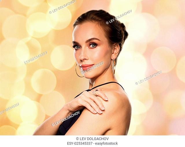 people, luxury, jewelry and fashion concept - beautiful woman in black wearing diamond earring and ring over lights background
