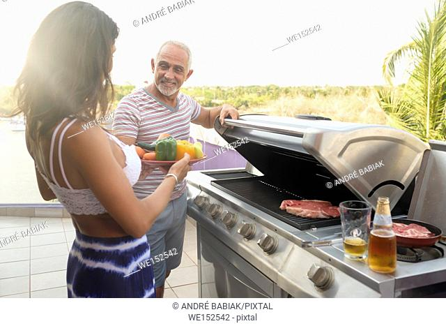 Woman bringing vegetables to a man grilling some meat outdoors