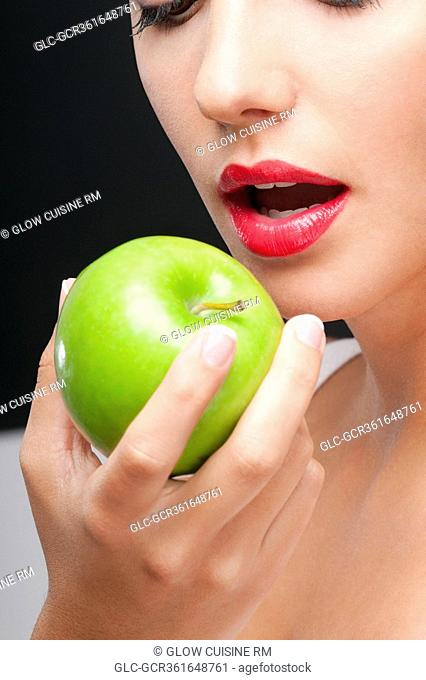 Close-up of a woman eating a granny smith apple