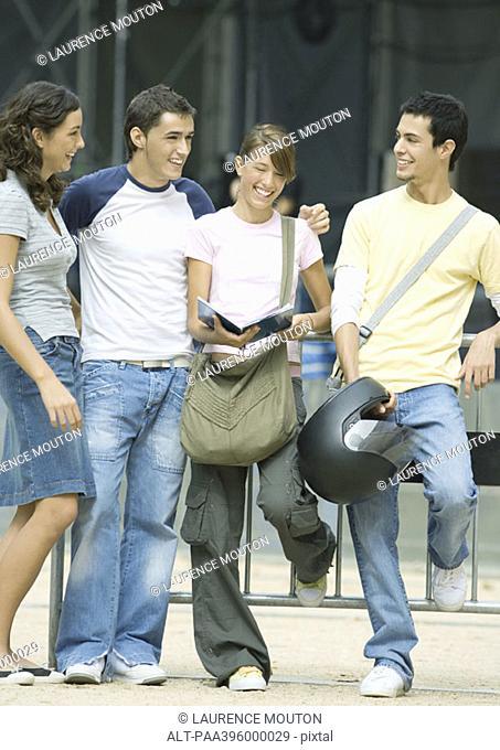 Teens standing outdoors, talking