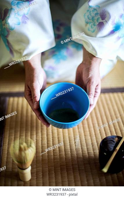 High angle close up of Japanese woman wearing traditional white kimono with blue floral pattern kneeling on floor during tea ceremony, holding blue tea bowl