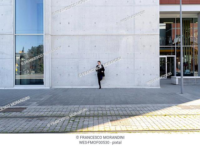 Italy, Florence, young businessman leaning against a building in the city