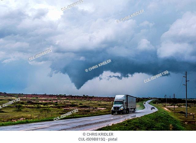 Truck on wet road, tornado lifting south of Waynoka in background, Oklahoma, USA