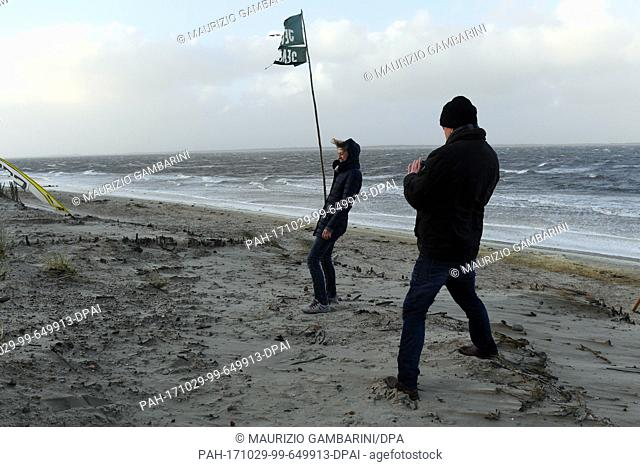 Tourists fight against the strong winds at the beach in Utersum, Germany, 29 October 2017. Photo: Maurizio Gambarini/dpa