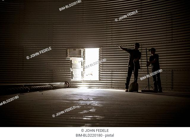 Caucasian father and on standing in empty silo