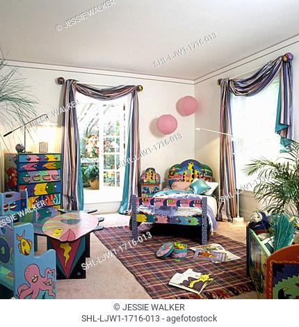 CHILDREN'S BEDROOM: Hand decorated furniture in primary colors, colorful striped window swags, area rug on pale pink square