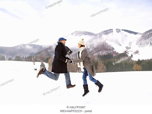 Happy senior couple jumping in the air in snow-covered landscape