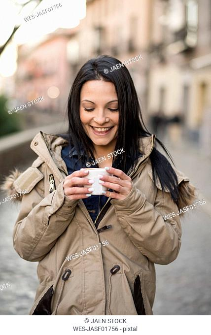 Spain, Granada, smiling young woman holding cup at Albayzin district